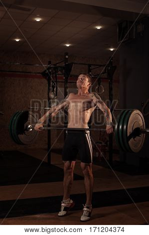Male muscular athlete lifting barbell in gym. Weightlifting, power lifting equipment. Sports, fitness - healthy lifestyle concept.