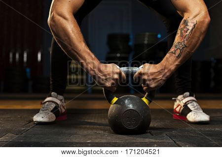 Cropped shot of male muscular athlete doing exercise with kettlebell. Sports, fitness concept.