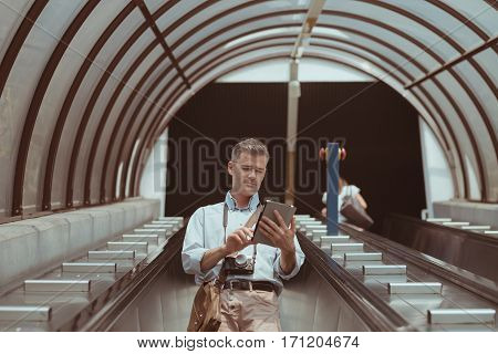 Man On The Escalator Using A Tablet
