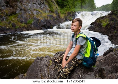 Teenager tourist with a backpack standing near the mountain waterfall.