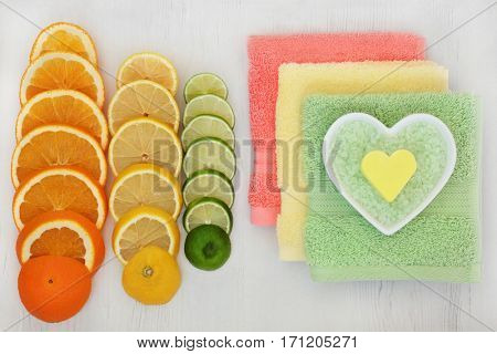 Citrus spa ingredients with orange, lemon and lime fruit, bath crystals and soap in heart shaped dish with flannels on distressed wood background.
