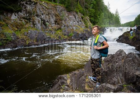 Teenager with a backpack standing near the waterfall
