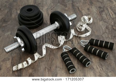 Body building equipment with dumbbell weights, hand grippers and tape measure over marble background.