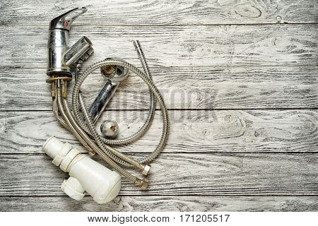 old broken faucet water on a wooden background top view copy space