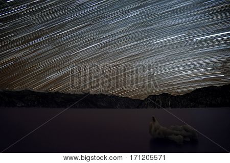 Beautiful night view with traces of stars in the form of tracks in the night sky on the background mountains with snow and sea with ice shot with a long exposure