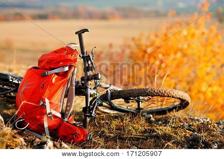 Mountain bike after ride in nature with backpack is on the hill. Sunny day in the countryside. A bicycle without people on a background of plane.