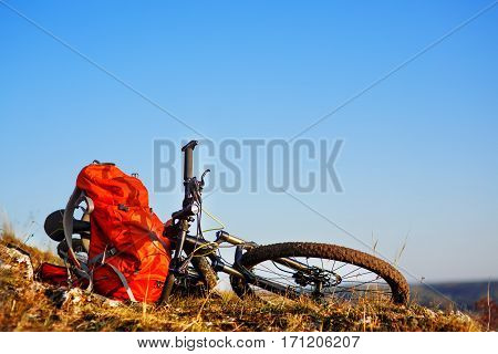 Mountain bike after ride in nature with backpack is on the hill. Sunny day in the countryside. A bicycle without people on a background of blue sky.