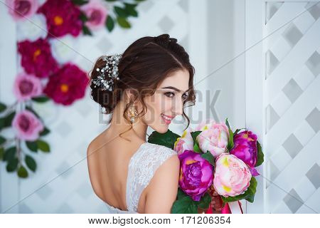 Classical beauty. Beautiful young woman with stylish brunette hair and elegant dress resting in luxury white classic room interior with folding screen and flowers. Spring portrait of elegant bride