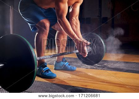 Young sporty man with naked torso clapping hands with chalk powder, preparing for weightlifting training. Power lifting equipment. Sports, fitness - healthy lifestyle concept.
