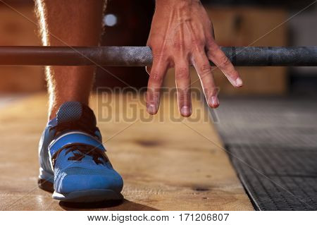 Closeup of male hand holding barbell before training. Power lifting, weightlifting equipment. Sports, fitness concept.