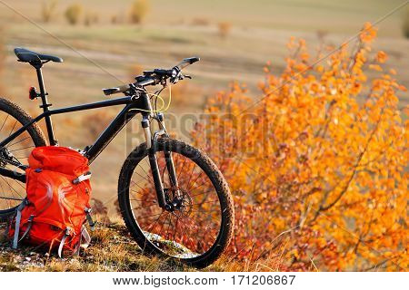 Mountain bike after ride in nature with backpack stands on the hill. Sunny day in the countryside. A bicycle without people on a background of plane.
