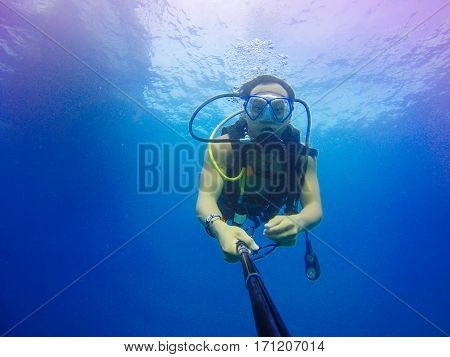 Underwater scuba diving selfie shot with selfie stick. Deep blue sea. Wide angle shot.