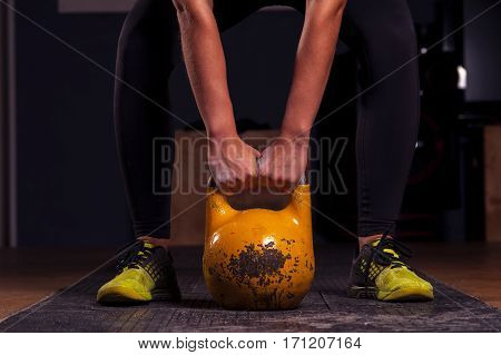 Cropped shot of female athlete preparing for kettlebell training. Power lifting, weightlifting workout. fitness, sports concept.