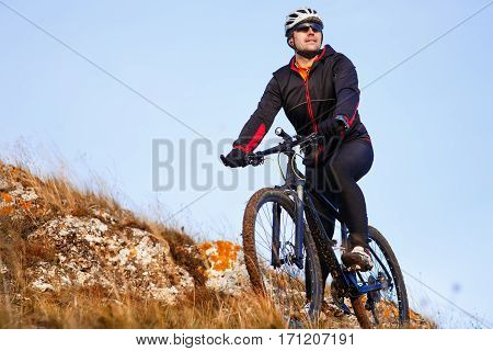 Mountain biker looking at inspiring mountain landscape, standing with bicycle. Man cycling MTB on the hill. Sport and active recreation, fitness motivation and inspiration. Blue sky background.