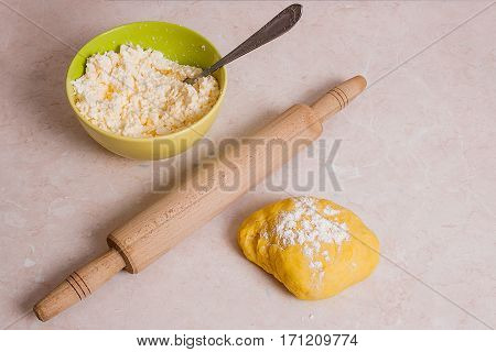 Rolling Pin And Yellow Dough With White Flour And Green Bowl With Cottage Cheese Or Curd On Light Ma