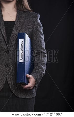Woman in suit holding folder with inscription Guidelines