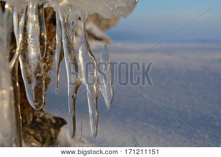 Siberia, winter. Lake Baikal icicles in rays of rising sun
