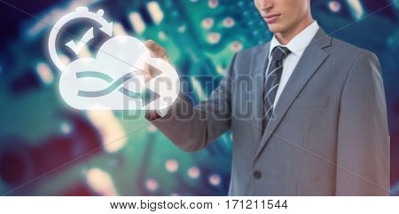 Midsection of elegant businessman pointing against blue printed circuit board