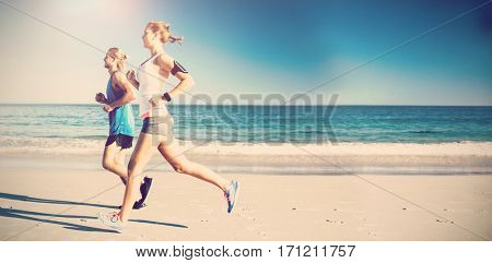 Side view of friends jogging at beach on sunny day