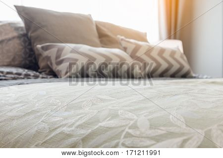 Green Blanket With Set Of Pillows On Cozy Bed In Bedroom