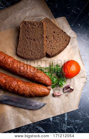 Close Up View Smoked Sausage With Spice, Herbs And Vegetables On The Packaging Paper. Vintage Knife