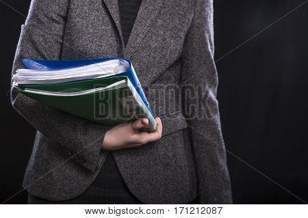 Office employee in suit with documents on black background.