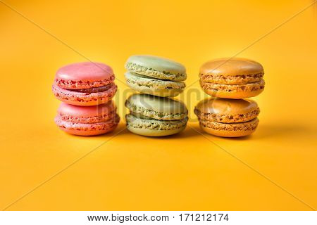 pink orange and green macarons on yellow background
