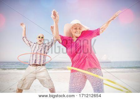 Senior couple doing hula hoop on beach