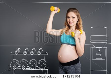 Live life fully. Cheeful content prenant woman smiling and doing sport exercises while holding dumbbels