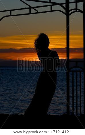 Woman silhouette in golden sunset with the sea background, dramatic sunset and alone woman, romantic mood, single alone woman in romantic atmosphere, romantic sunset,  woman in asia, summer holidays