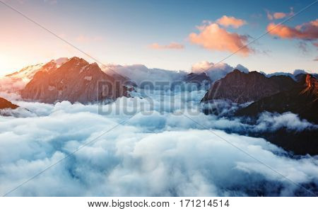 Creamy fog covered the famous glacier Marmolada in morning light. Picturesque and gorgeous scene. Location place Val di Fassa valley, passo Sella, Dolomiti, South Tyrol. Italy, Europe. Beauty world.