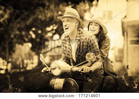 Grey background against cheerful couple riding moped