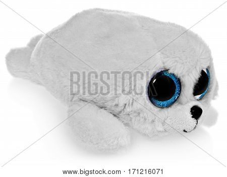 Plush toy a white seal with big blue eyes. Furry pet gift lies on a white background at an angle with a slight shadow and reflection.