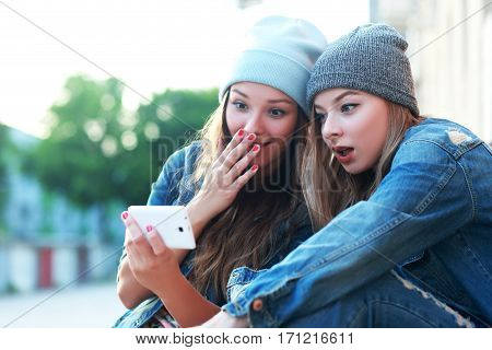 Euphoric friends watching videos on a smartphone and pointing at screen surprised and laughing