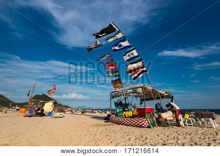 Rio de Janeiro, Brazil - January 27, 2017: Many colored flags waving in the wind above the tent in Copacabana beach.