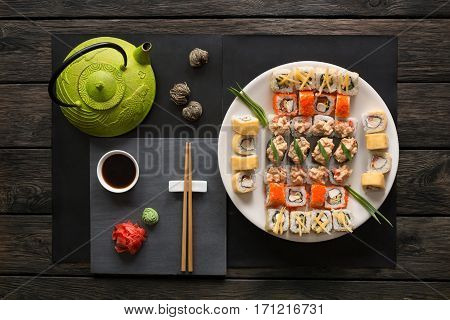 Japanese food restaurant, sushi maki gunkan roll platter. Teapot and black slate plate with chopsticks, ginger, soy, wasabi. Top view with copy space on rustic wood background