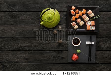 Japanese food restaurant, sushi maki gunkan roll set or platter. Green teapot and black slate plate with chopsticks, ginger, soy, wasabi. Top view with copy space on rustic wood background