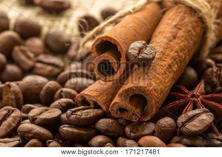 coffee beans cinnamon sticks and cinnamon on burlap background.