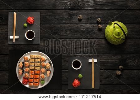 Japanese food restaurant, sushi maki gunkan roll set for two or platter. Green teapot and black slate plates with chopsticks, ginger, soy, wasabi. Top view with copy space on rustic wood background