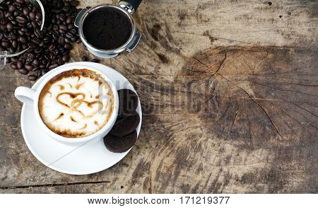 Heart latte art. Cappuccino coffee. A cup of latte, cappuccino or espresso coffee with milk put on a wood table with dark roasting coffee beans. Drawing the foam milk on top.