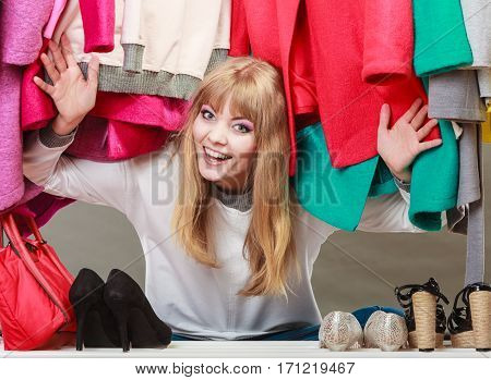Pretty woman sitting on the floor under clothing from wardrobe. Young happy undecided shopper girl bought new clothes. Shopaholic concept.