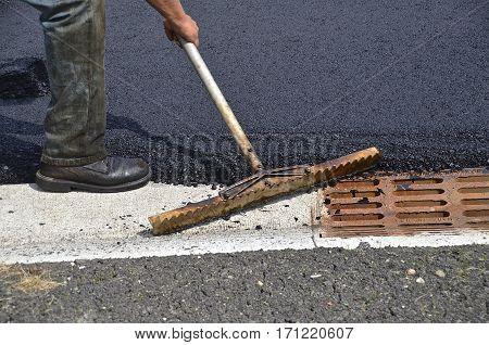 Spreading asphalt around a street water drain