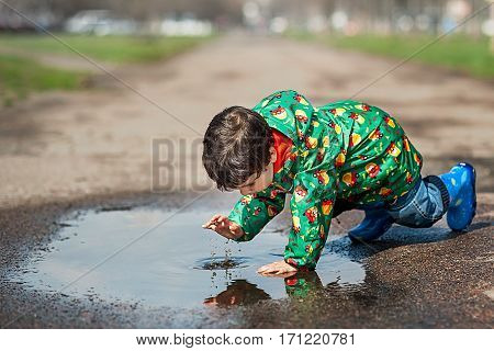Little boy in raincoat and rubber boots playing in puddle
