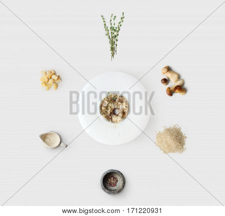 Cooking italian food, risotto with wild mushrooms, isolated on white background. Rice, fungus, sauce, parmesan and other ingredients around plate with dish ready