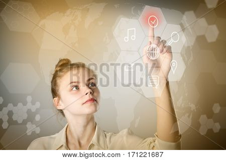Young slim woman in white is pushing the virtual hexagonal button. Innovative technology concept. Warm background.