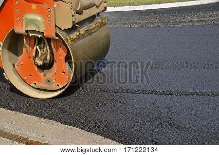A heavy roller packs the wet asphalt on a street construction project