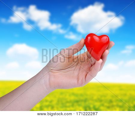 Hand holding red heart on the background blurry landscape with blue sky.