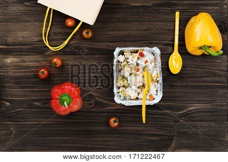 Came from shopping. Yellow spoon standing in box with stewed rice and vegetables yellow pepper and spoon lying in right corner