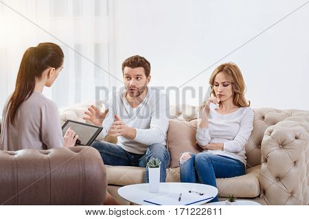 Family problems. Nice cheerless blonde woman sitting next to her husband and holding a tissue while visiting a psychologist with him