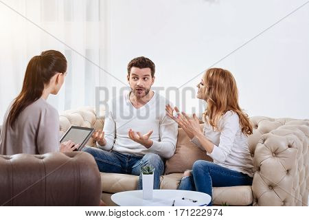 Trying to help. Nice female dark haired psychologist sitting in the armchair and holding a tablet while listening to her patient